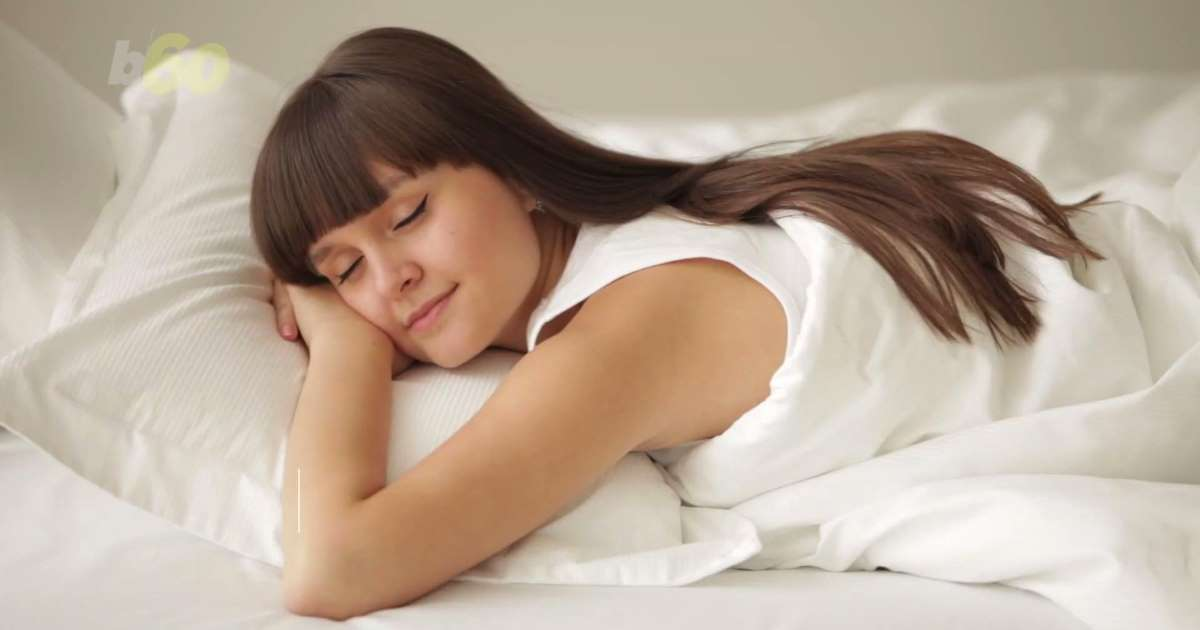 A girl sleeping on a white bed
