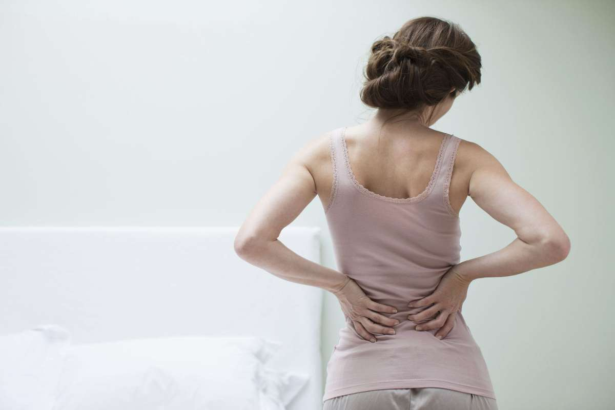 A young woman feeling the back pain