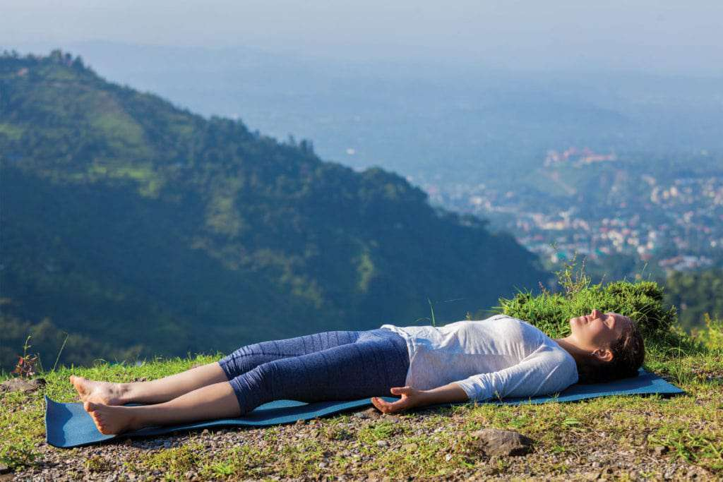 A woman practicing yoga nidra in nature