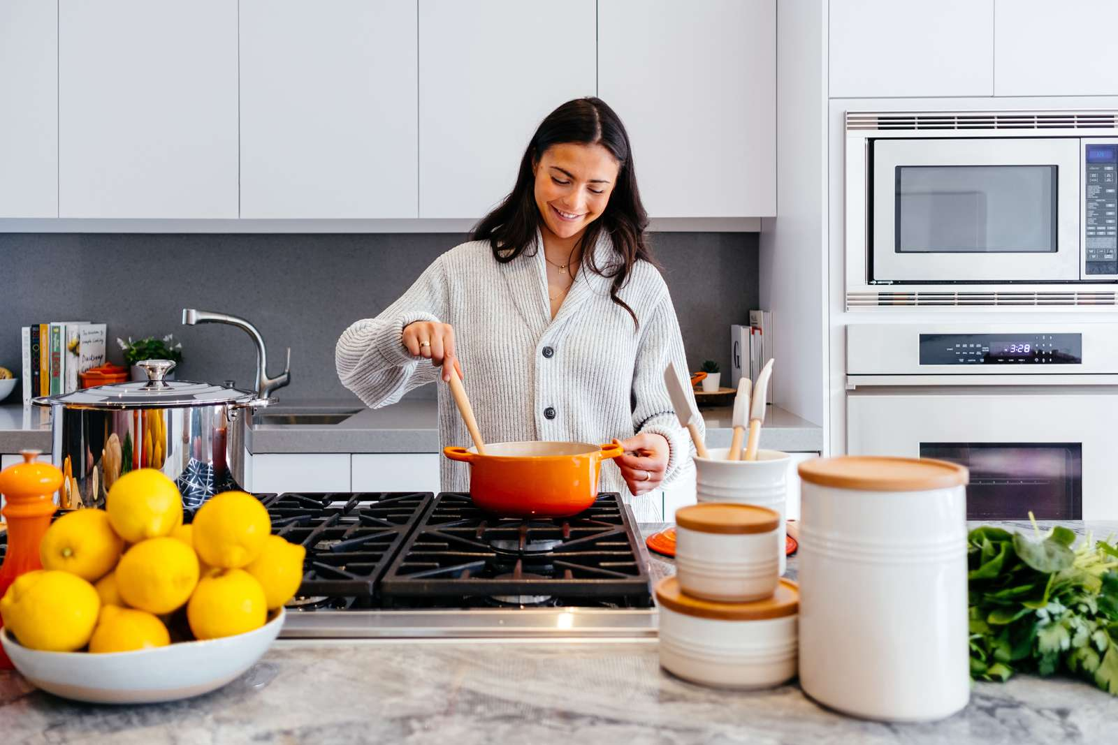 A woman cooking food in an elegant kitchen