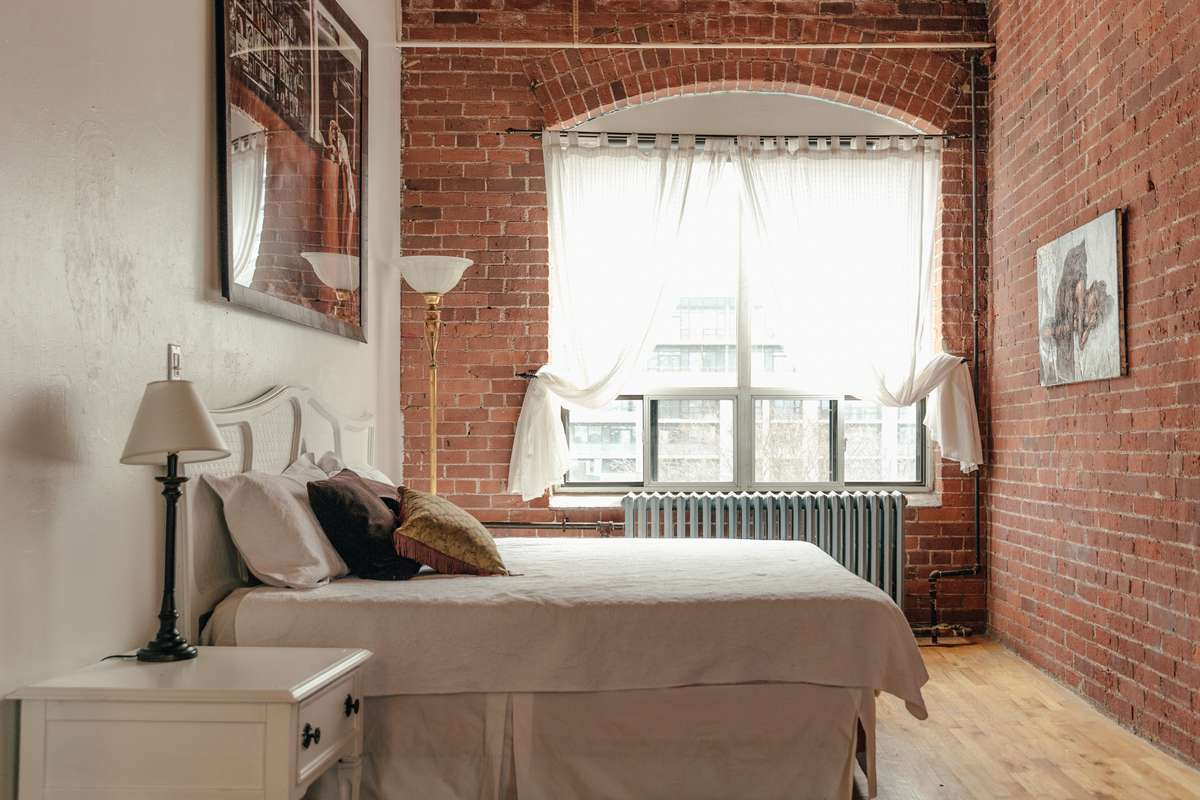 A bedroom with a window from where the sunlight comes easily