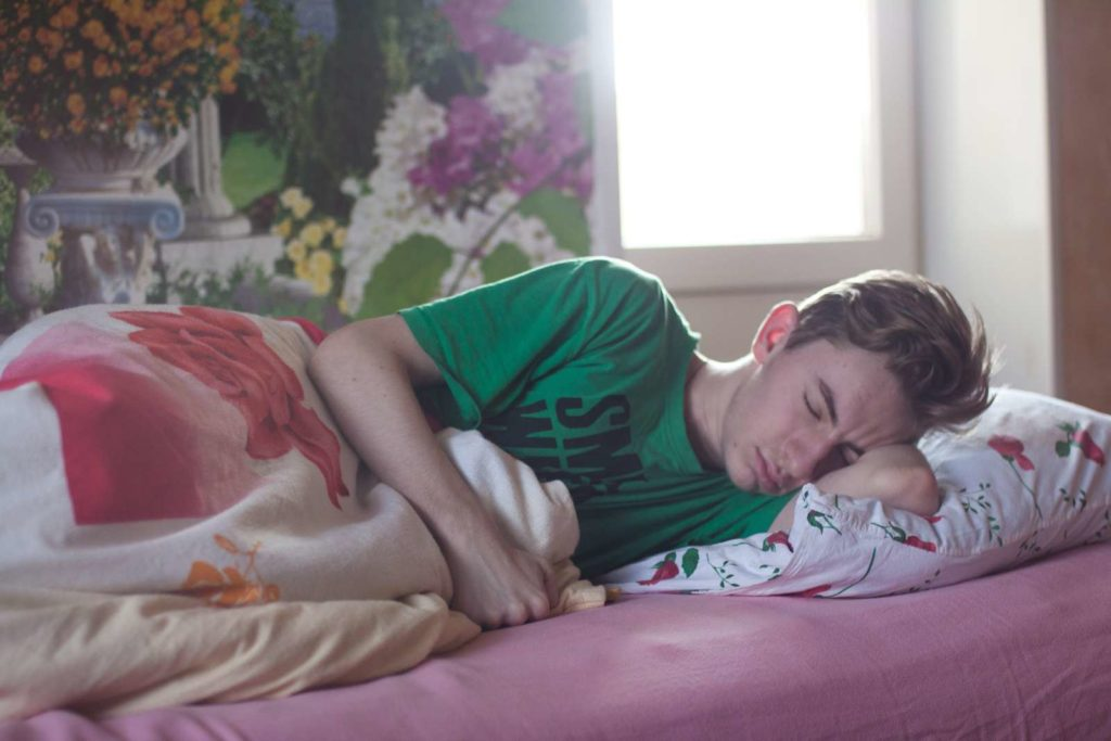 A man in green t shirt sleeping on bed