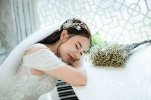 photo-of-woman-taking-a-nap-on-top-of-piano