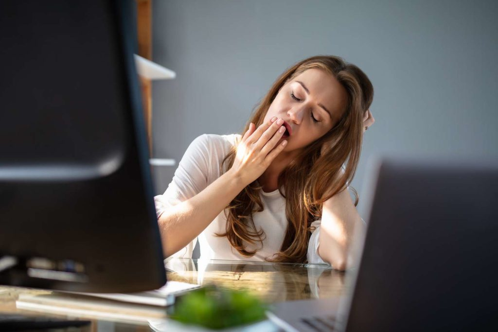 A girl yawning while working in front of desk